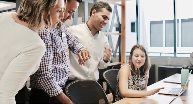 team around laptop talking about workforce management capabilities