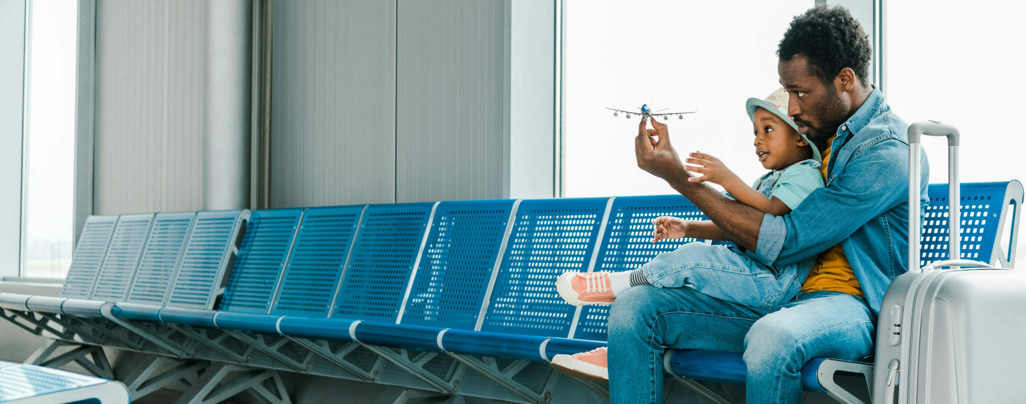 man and child playing with airplane from travel and hospitality industry